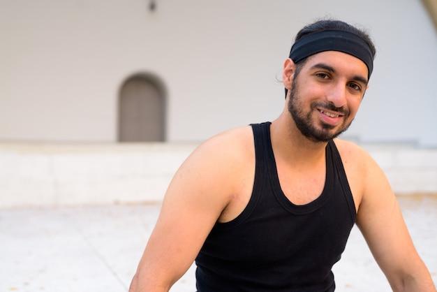 Visage d'heureux jeune bel homme indien barbu souriant dans les rues à l'extérieur