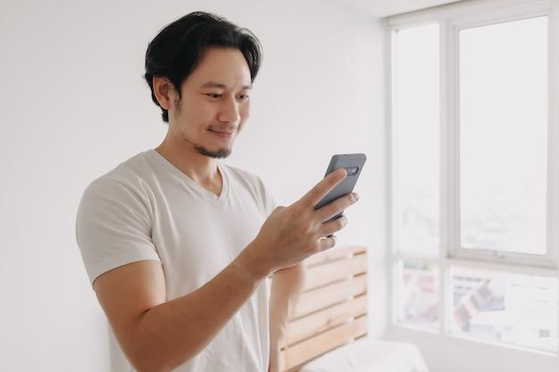 Visage heureux et souriant de l'homme utilisant un smartphone