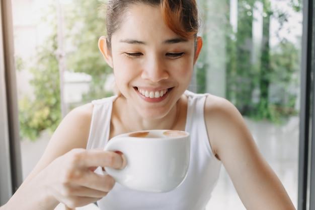 Visage heureux de sourire de femme admire le moment avec une tasse de café