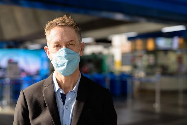 Visage d'homme d'affaires mature avec masque pour se protéger contre l'épidémie de coronavirus à la gare du ciel