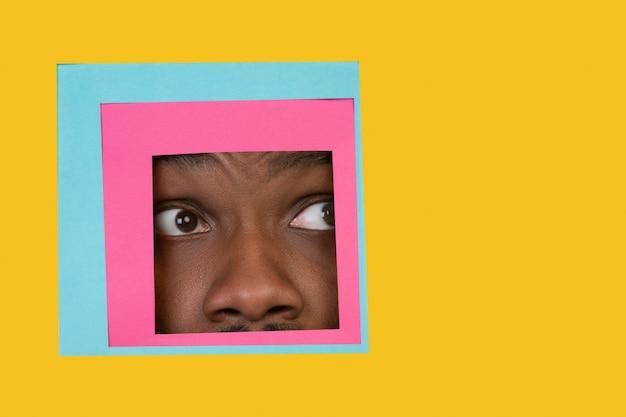 Visage d'homme afro-américain jetant un coup d'œil à travers la place en fond jaune