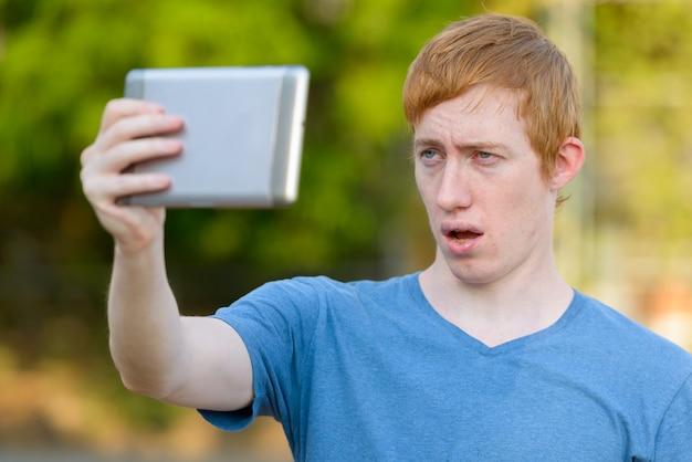 Visage d'homme aux cheveux rouges prenant selfie avec tablette numérique dans le parc
