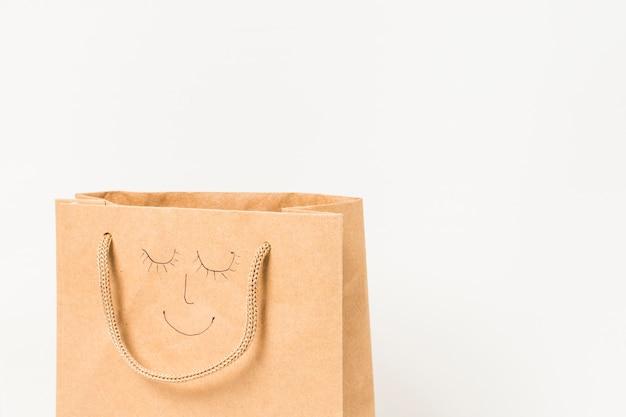 Visage humain dessiné sur un sac en papier brun contre une surface blanche