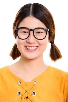 Visage de jeune femme asiatique heureuse souriant tout en portant des lunettes