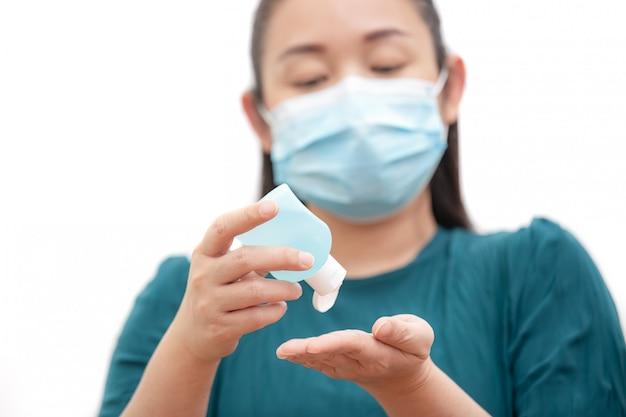 Le visage d'une jeune femme asiatique lave le gel pour les mains, assainit et porte un masque pour éviter les germes, les fumées toxiques et la poussière. prévention des infections bactériennes