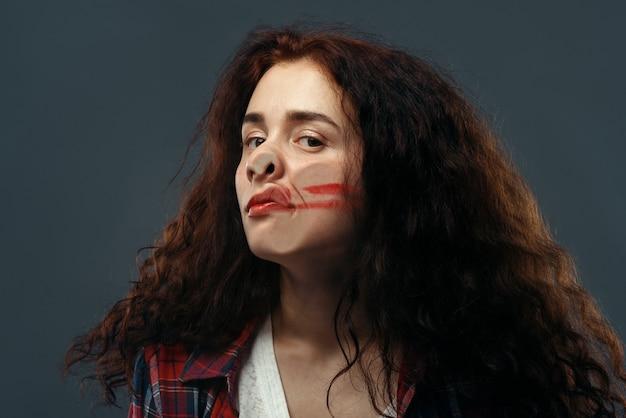 Visage de jeune femme écrasé sur du verre transparent, fille avec du rouge à lèvres barbouillé.