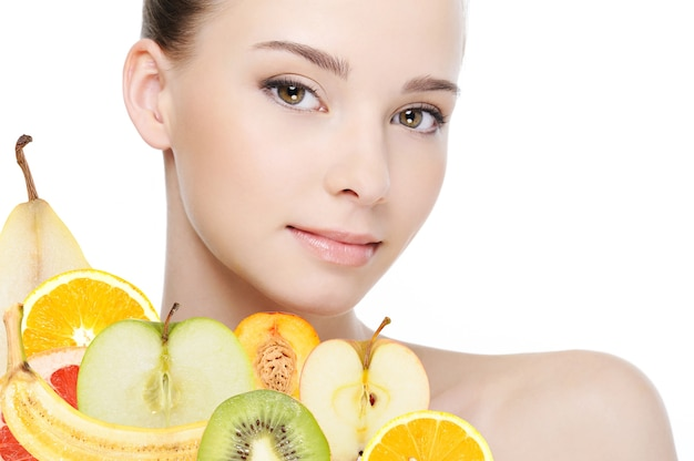 Visage de jeune femme avec des fruits frais isolé sur blanc
