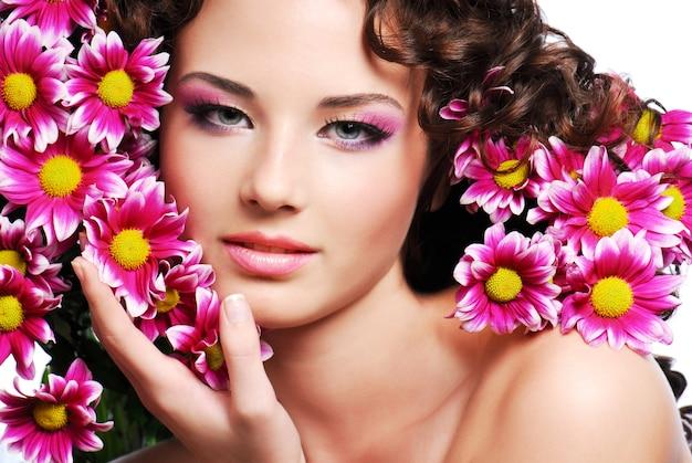 Visage de jeune femme séduisante avec des fleurs