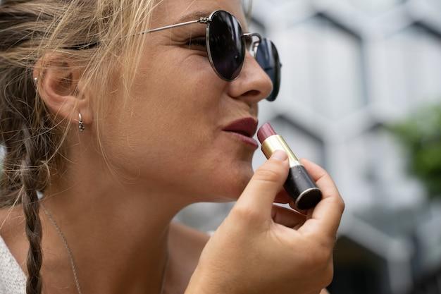 Visage d'une jeune fille blonde utilisant le mobile comme miroir tout en se maquillant