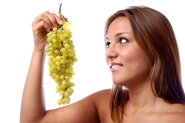 Le visage d'une jeune fille en gros plan, une grappe de raisin vert mûr