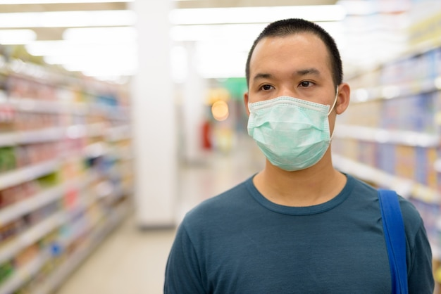 Visage de jeune homme asiatique avec masque shopping à distance au supermarché
