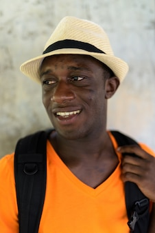 Visage de jeune homme touriste heureux souriant et pensant contre le mur de béton dans le ciel de la gare de bangkok en thaïlande