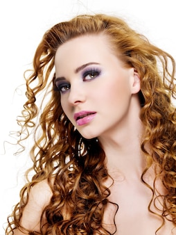 Visage de jolie jeune femme avec de longs poils de beauté et élégant maquillage violet - isolé sur blanc