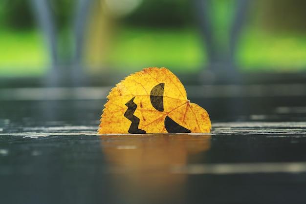Un visage malicieux peint sur une feuille coincée dans un arbre. vacances d'halloween.
