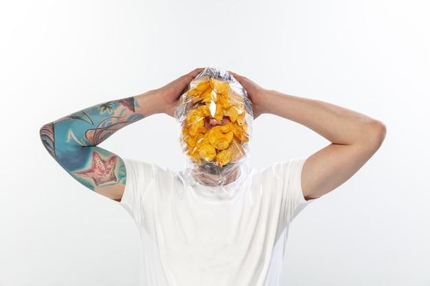 Visage masculin recouvert de toile cirée, de cellophane et d'aliments malsains, difficile à respirer. les gens ont perdu leur visage, ne peuvent pas remarquer la pollution de l'environnement qu'ils font eux-mêmes. ordures, problème, respiration.