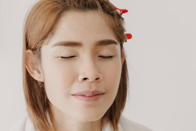 Le visage nu d'un modèle de femme asiatique se prépare à être maquillé par l'artiste