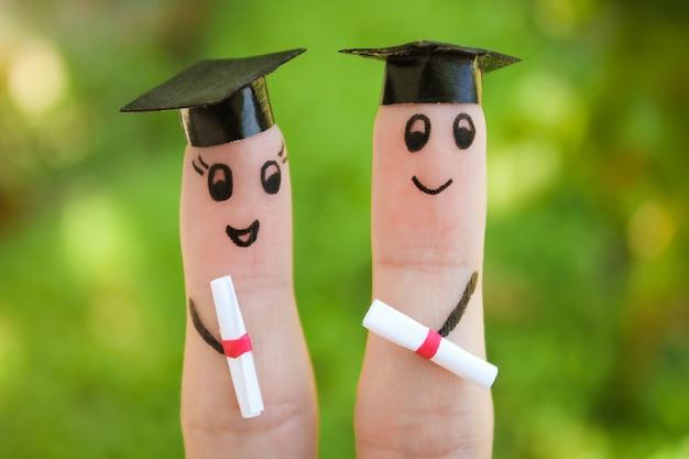 Visage peint sur les doigts. étudiants titulaires de leur diplôme