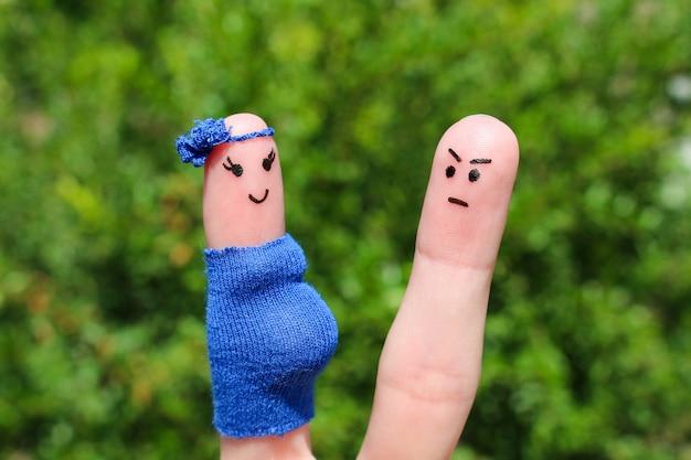 Visage peint sur les doigts. l'homme était bouleversé parce que la femme était enceinte