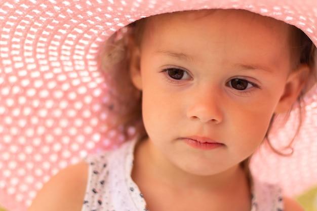 Visage d'une petite fille mignonne 1-3 dans un chapeau à larges bords d'été rose en été