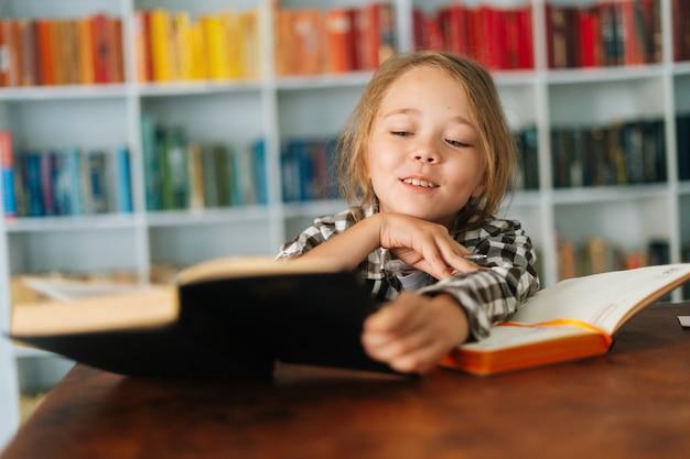 Visage de plan rapproché d'enfant gai d'écolière d'élève faisant des devoirs lisant un livre de papier assis à table dans