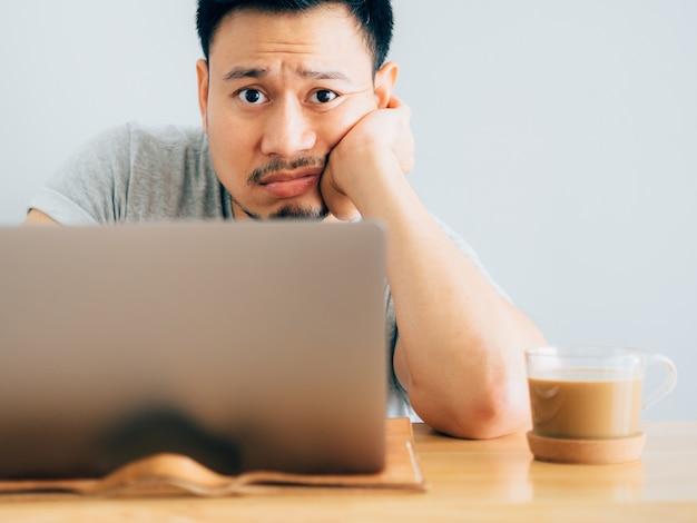 Visage sérieux et ennuyeux de l'homme travaille sur ordinateur portable.