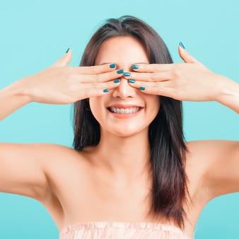 Visage souriant belle femme asiatique ses yeux couvrant par les mains