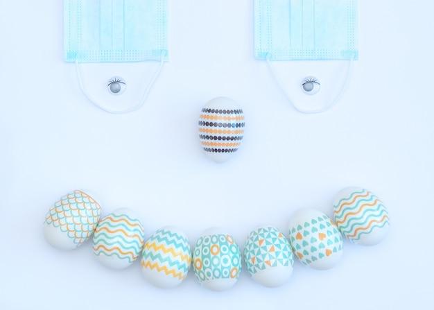 Visage souriant fait d'oeufs de pâques décorés et masques médicaux sur blanc