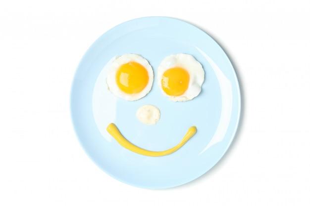 Visage souriant fait de plaque avec des œufs au plat isolé