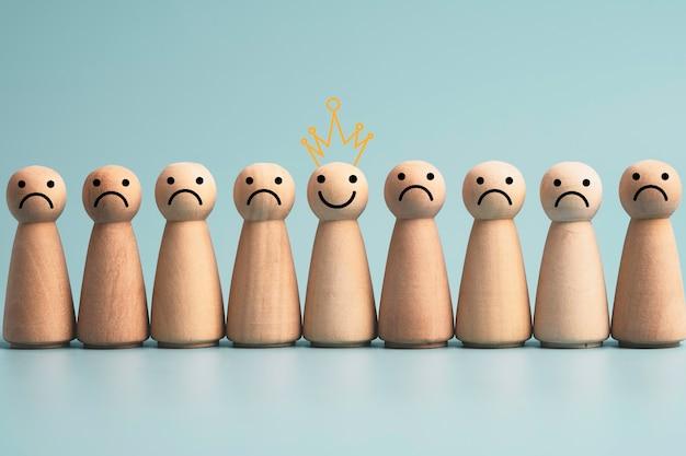 Visage souriant sur une figure en bois parmi une figure en bois de tristesse sur fond bleu, emotion sélectionne l'état d'esprit et le concept de bonheur.