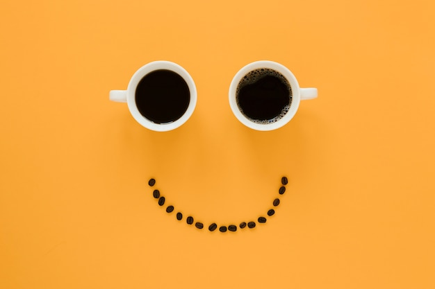Visage souriant des tasses à café et des haricots