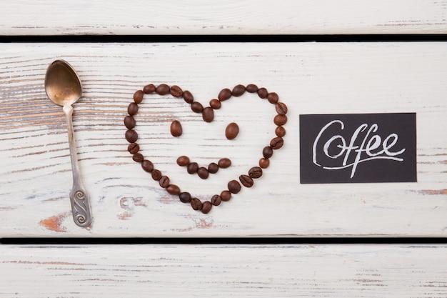 Visage souriant avec tête en forme de coeur et cuillère à café. surface en bois blanc.