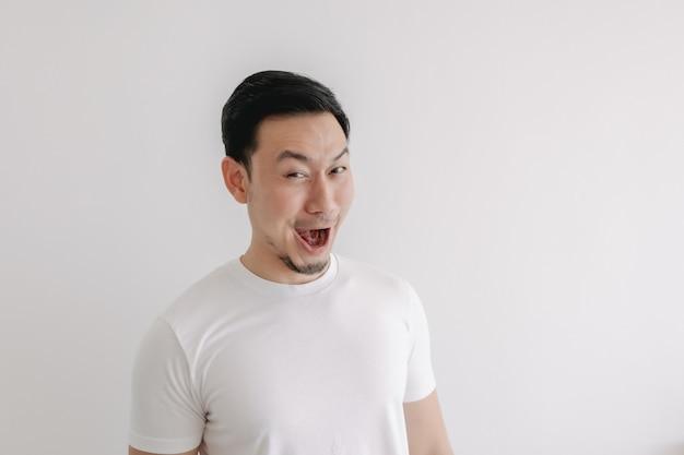 Visage de sourire drôle de sourire de l'homme en t-shirt blanc isolé sur mur blanc