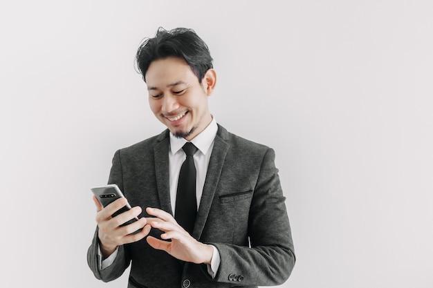 Visage de sourire heureux d'homme d'affaires utilise un smartphone dans le concept d'application commerciale