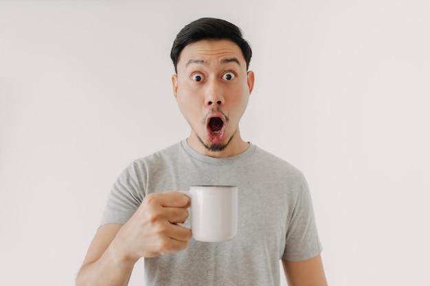 Visage surpris de l'homme boit une tasse de café isolé sur fond blanc