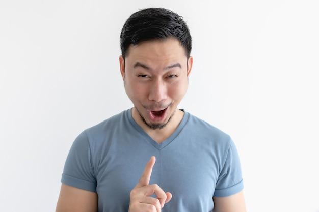 Visage surpris et wow de l'homme en t-shirt bleu sur un mur isolé.