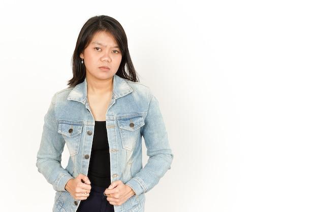 Visage triste en colère de la belle femme asiatique portant une veste en jean et une chemise noire isolée sur blanc