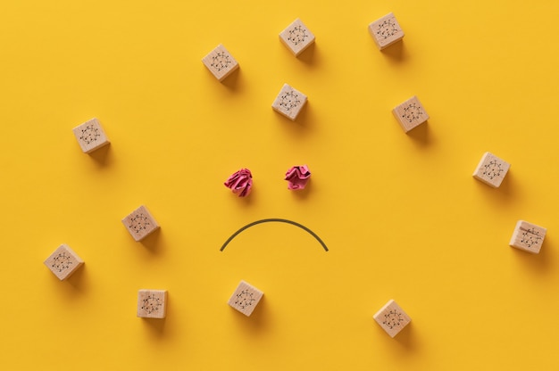 Visage triste dessiné sur fond jaune avec de nombreux blocs de bois avec des molécules covid19 autour d'eux.