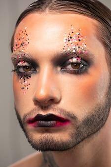 Visage de triste jeune homme barbu avec des paillettes colorées sur le visage et les lèvres noires, concept d'acteur musical