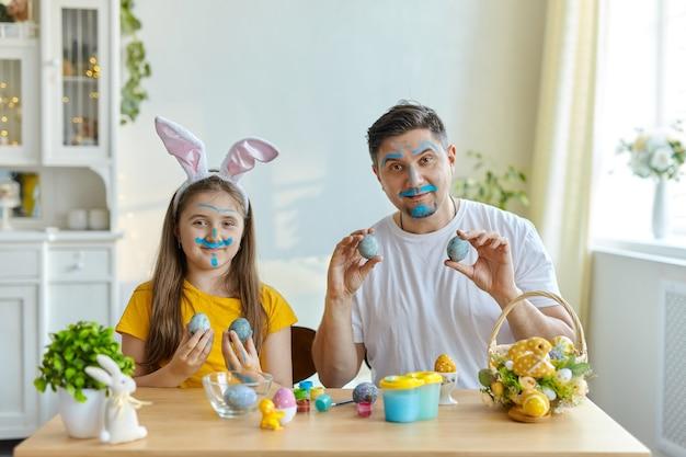 Les visages de papa et de fille tachés de peinture bleue pour peindre des œufs. sur la table se trouve un panier avec des œufs de pâques et des peintures.