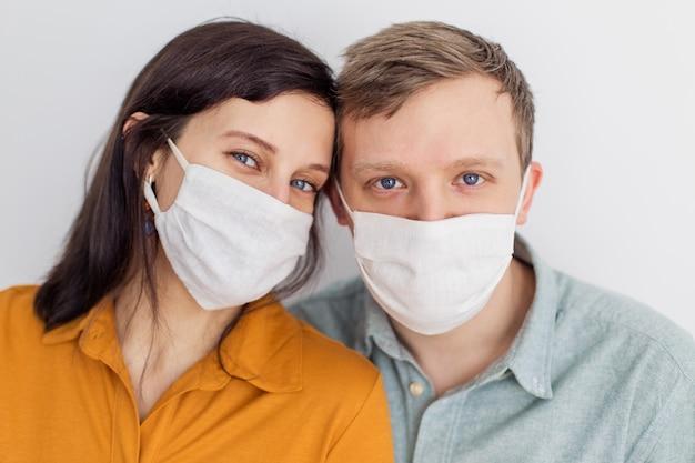 Visages de personnes dans des masques de protection contre les coronavirus fabriqués à la main. un beau couple aux yeux bleus en quarantaine se protégeant d'une pandémie. jeunes jeunes positifs. lifestyle covid-19 à la maison ensemble