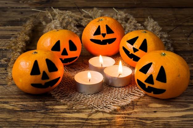 Visages rigolos peints sur des mandarines autour de bougies allumées pour halloween