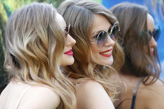 Les visages de trois modèles. femmes en lunettes de soleil