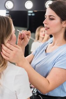 Visagiste maquillant les sourcils du client