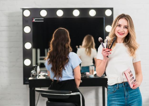 Visagiste tenant des pinceaux à maquillage et une palette d'ombres à paupières