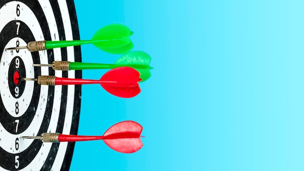 Visez avec la flèche au centre. cible avec des fléchettes rouges et vertes au centre sur un fond bleu clair. atteindre la cible.