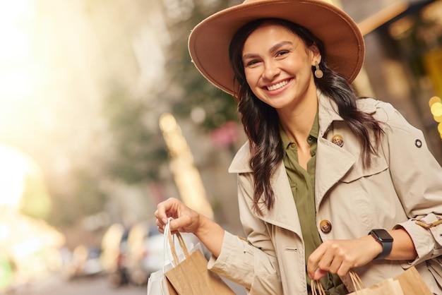Visite de la boutique de mode portrait d'une jeune femme excitée portant un manteau gris et un chapeau portant