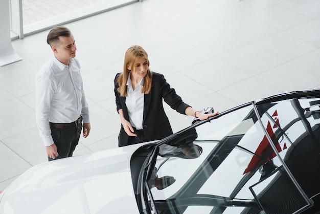 Visite d'un concessionnaire automobile. beau couple tient une clé de leur nouvelle voiture et souriant, la jeune fille embrasse son mari dans la joue