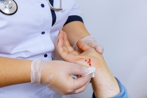 Visite du patient médecin de blessure à la main essuie le sang nettoyant une plaie