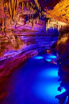 Visite d'une grotte au milieu de la rivière avec des lumières bleues et des formations de stalactites
