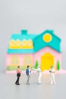 Visite médicale d'epi de personnes miniatures pour vérifier le coronavirus à la maison, concept de soins de santé